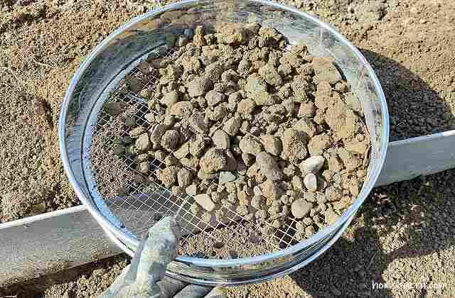 畑づくりで石をふるいで取り除いている場面